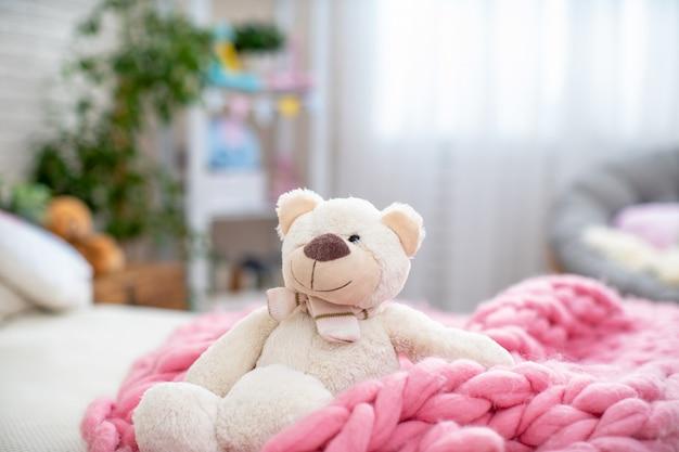 Witte zachte teddybeer, zittend in zachte merino deken, op bed