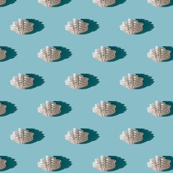 Witte zeeschelp naadloze patroon met harde schaduw op lichtblauwe achtergrond. zomerseizoen en zee vakantie concept. natuur achtergrond