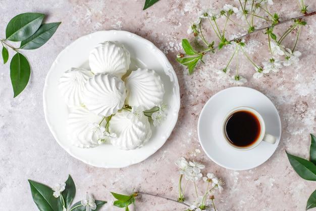 Witte zefier, heerlijke marshmallows met lentebloesem bloemen, bovenaanzicht