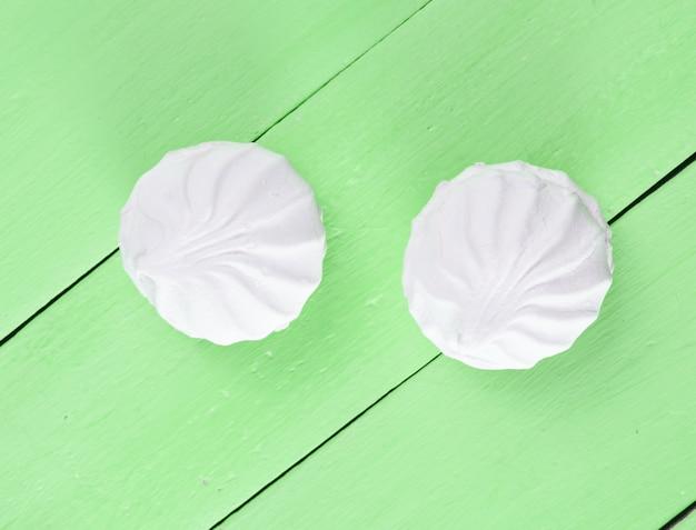 Witte zefierkoekjes op groene houten lijst