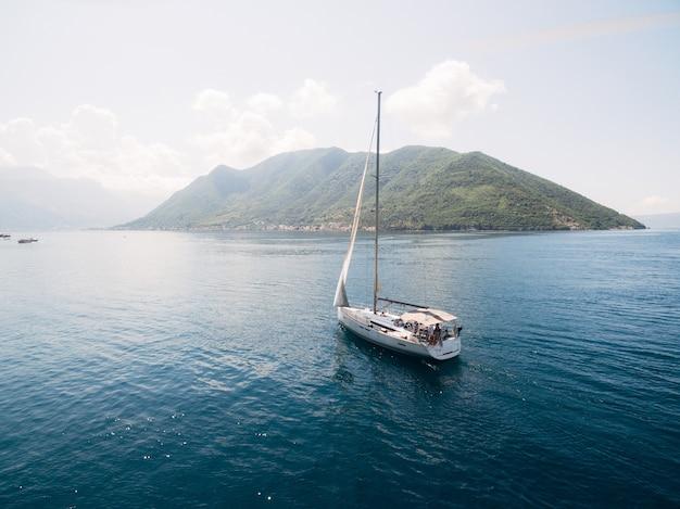 Witte zeilboot op het water nabij de bergen van de stad perast.