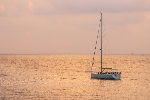 Witte zeilboot van toerist met zonsonderganghemel op het ao thaise zeegebied rond haad bangbao.