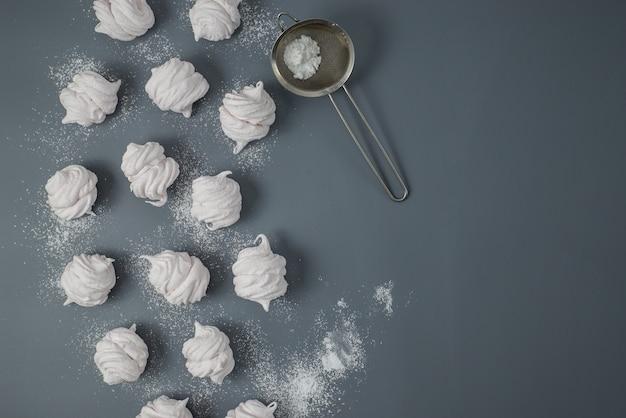 Witte zelfgemaakte zefir of marshmallow met poedersuiker op grijze achtergrond