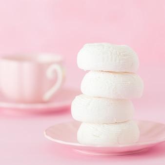 Witte zephyr dessrt op roze plaat, kopje koffie met melk op pastel roze achtergrond.