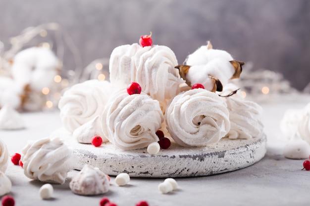 Witte zephyr op grijze betonnen ondergrond set van zelfgemaakte marshmallow meringue, viooltje. russische zoetheidskeuken