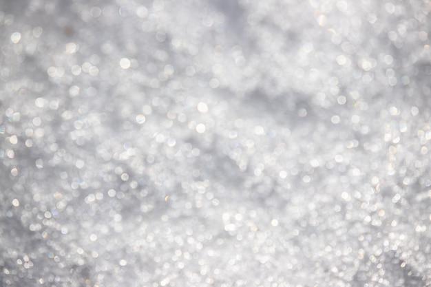 Witte zilverachtige textuur van onscherpe sneeuw. heldere gevlekte bokeh.