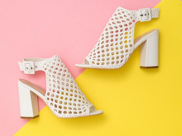 Witte zomer mode damesschoenen op roze en geel oppervlak