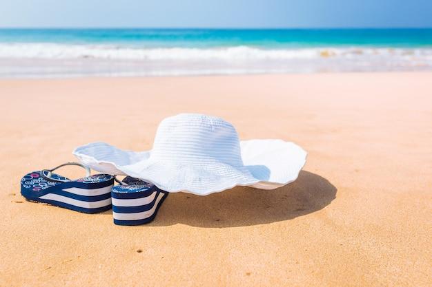 Witte zomerhoed, zonnebril en slippers over het zand op een tropisch strand