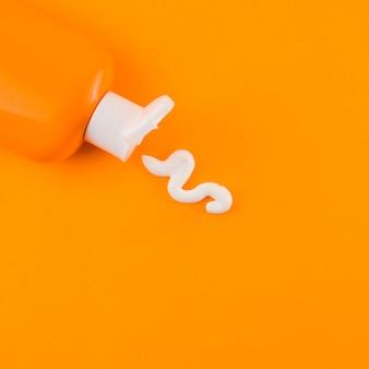 Witte zonnebrandcrème die uit oranje fles tegen een oranje achtergrond komt