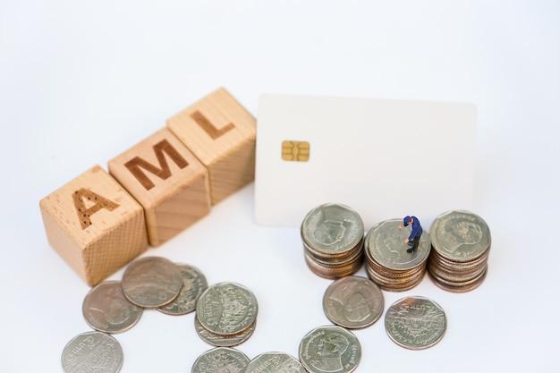 Witwassen van geld concept. miniatuurmensen, officier die stapel munten onderzoekt en houten woordblok