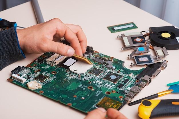 Wizard repareert laptop met gereedschap en handen