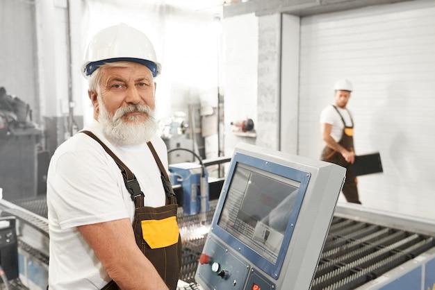 Wlder mannelijke arbeider van metaalfabriek die zich dichtbij computer bevindt