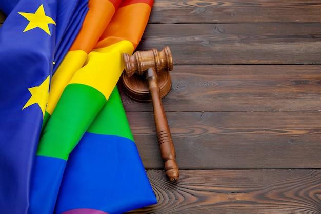 Woden rechter hamer symbool van wet en rechtvaardigheid met lgbt vlag in regenboogkleuren op houten