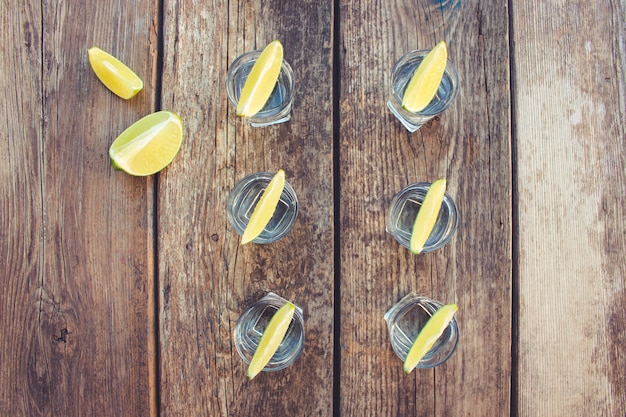 Wodka en kalkplakken op houten achtergrond.