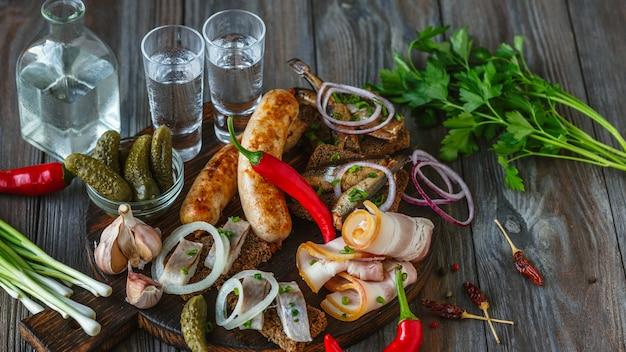 Wodka en traditionele snack op houten muur