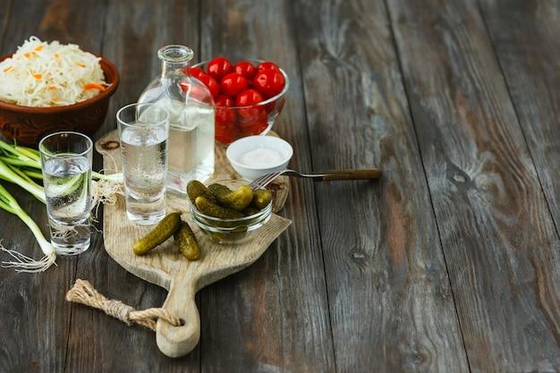 Wodka en traditionele snacks op houten vloer Gratis Foto