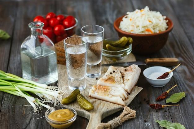Wodka en traditionele snacks op houten vloer