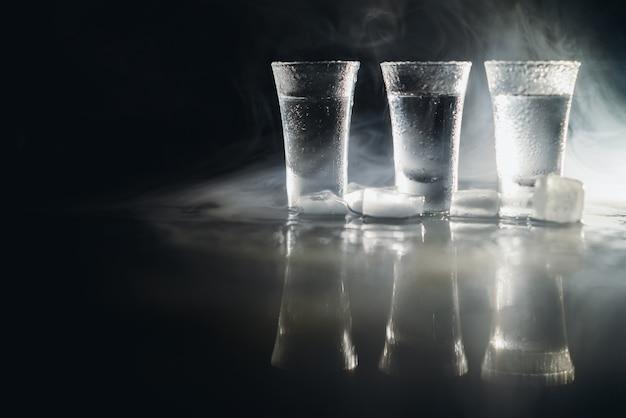 Wodka in borrelglaasjes op donkere achtergrond.