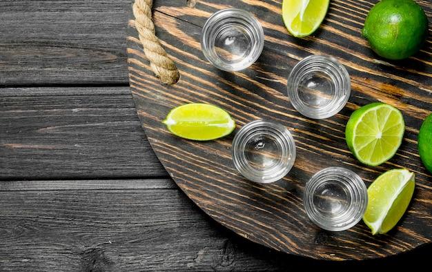 Wodka in een borrelglas op een dienblad met schijfjes limoen. op houten