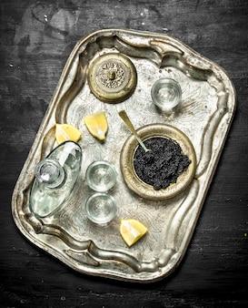 Wodka met kaviaar op het oude dienblad. op een zwart bord.