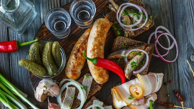 Wodka met reuzel, gezouten vis en groenten, worstjes op houten muur.