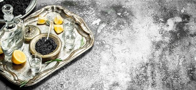Wodka met zwarte kaviaar en citroen op rustieke tafel.