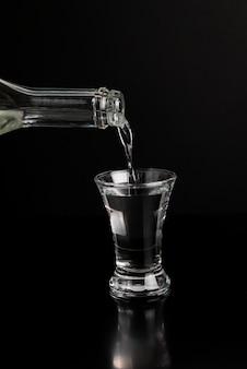 Wodka wordt uit een fles in een glas op een zwarte tafel gegoten