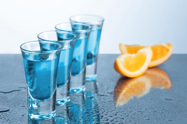 Wodkaglas met ijs op blauw