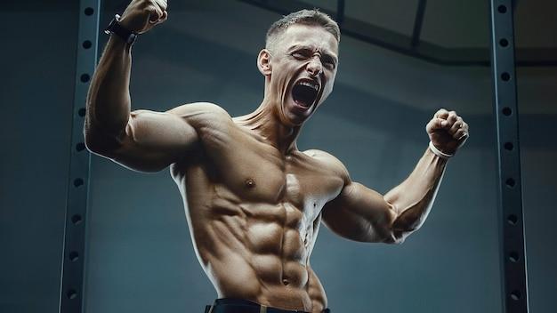 Woede schreeuw. energie kaukasische sterke atleet schreeuwen in de sportschool tijdens de training van abs. fitness, bodybuilding en gezondheidszorgconcept