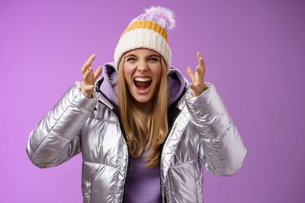 Woedend beu pissige blonde vrouw schreeuwen hardop hatelijk voorover buigen handen schudden gebrek aan respect boos ruzie diepbedroefd huilen staande gehinderd ruzie, paarse achtergrond. Premium Foto
