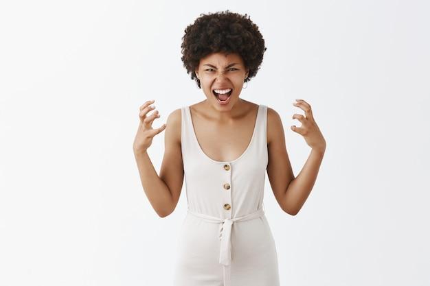 Woedend en boos stijlvol meisje poseren tegen de witte muur