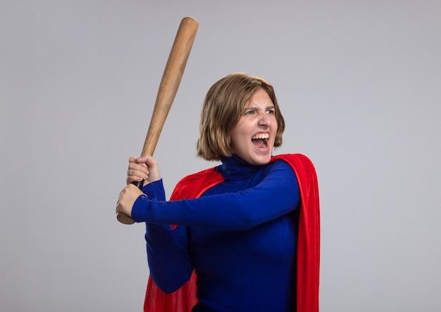 Woedend jong blond superheld meisje in rode cape houden honkbalknuppel kant klaar om te raken schreeuwen geïsoleerd op witte muur met kopie ruimte kijken