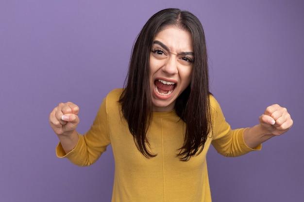 Woedend jong mooi kaukasisch meisje schreeuwend met gebalde vuisten geïsoleerd op paarse muur
