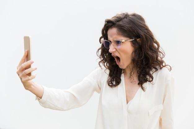 Woedend overdreven vrouw in glazen staren naar telefoonscherm