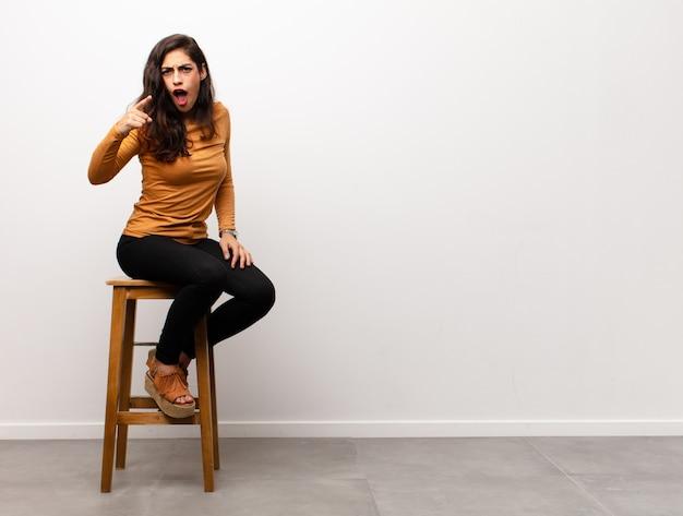 Woedend schreeuwende jonge vrouw zittend op een stoel naast copyspace