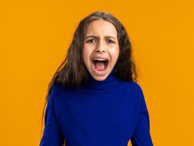 Woedend tienermeisje schreeuwen geïsoleerd op oranje muur