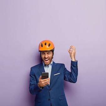 Woedend zakenman poseren in stijlvol pak en rode helm op kantoor