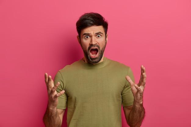 Woedende bebaarde man gebaart boos, roept luid uit, houdt zijn mond open, heeft last van een ontevreden uitdrukking, heeft een hekel aan iemand, grimassen hatelijk, poseert tegen roze muur