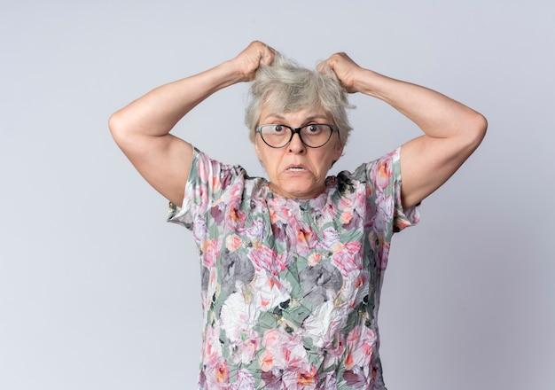 Woedende bejaarde vrouw in optische bril houdt en heft haar op zoek geïsoleerd op een witte muur