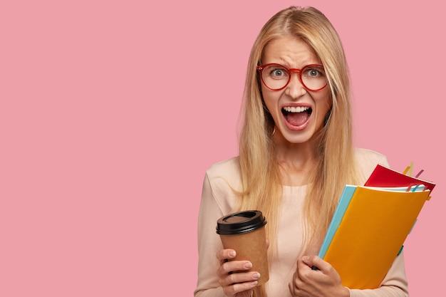 Woedende blonde vrouw schreeuwt van waanzin, ontevreden over examenresultaten na lange voorbereiding