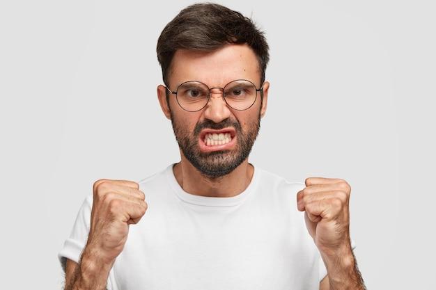 Woedende, boze europese man balt tanden en vuisten van woede, probeert zijn negatieve emoties te beheersen