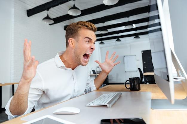 Woedende boze jonge zakenman die met computer werkt en schreeuwt