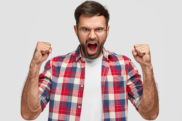 Woedende boze man met geïrriteerde uitdrukking, grijpt boos vuisten, schreeuwt tegen iemand, draagt een geruit overhemd, staat tegen een witte muur. negatieve menselijke emoties en gevoelens. lichaamstaal
