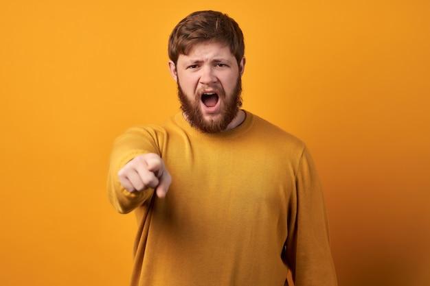 Woedende, boze ongeschoren man verliest zijn humeur, wordt gek, schreeuwt van irritatie en wijst naar je, geeft iemand de schuld en drukt negatieve emoties uit, draagt vrijetijdskleding, geïsoleerd op roze achtergrond