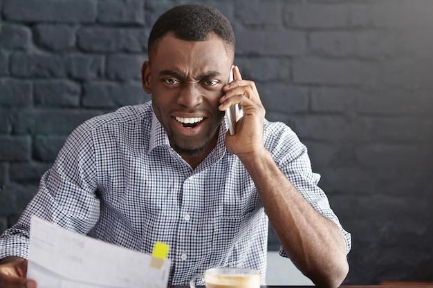 Woedende en gekke jonge afro-amerikaanse zakenman die bij slimme telefoon schreeuwt