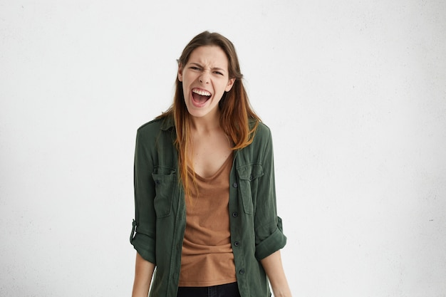 Woedende europese vrouw met steil haar draagt groen jasje schreeuwen in wanhoop met slecht humeur uiting van haar irritatie terwijl fronsen haar gezicht geïsoleerd