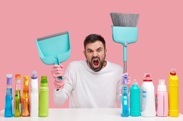 Woedende geïrriteerde ongeschoren man bezig met het schoonmaken van huis, draagt schep en bezem, zit aan tafel met schoonmaaksprays