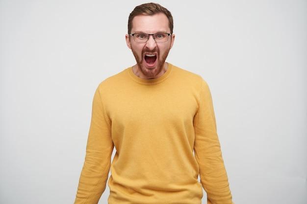 Woedende jonge bebaarde man met bruin kort haar kijkt en schreeuwt heftig met brede mond geopend, gekleed in mosterdtrui terwijl hij staat