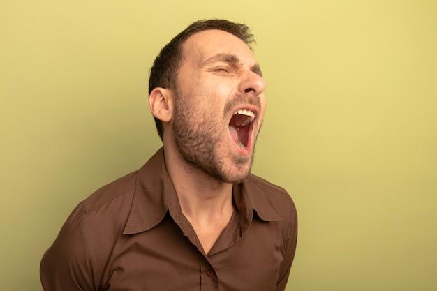 Woedende jonge blanke man schreeuwen met gesloten ogen geïsoleerd op olijfgroene achtergrond met kopie ruimte