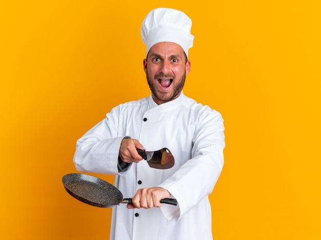 Woedende jonge blanke mannelijke kok in chef-kok uniform en pet kijken camera met koekenpan wijzend op camera met hakmes schreeuwen geïsoleerd op oranje muur met kopie ruimte